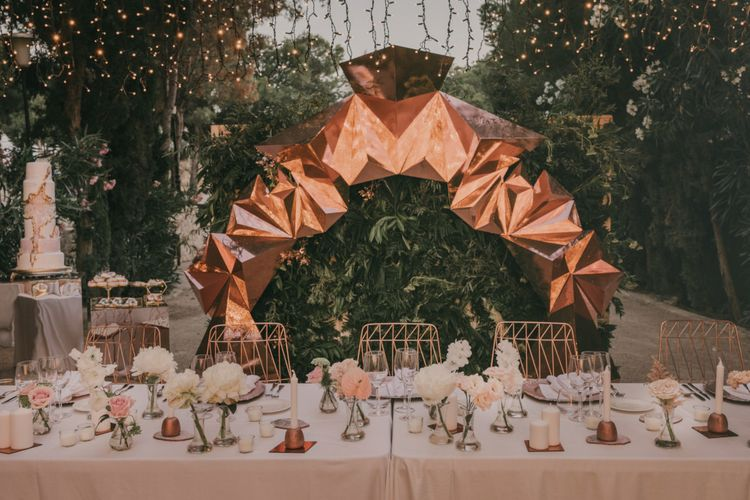 Top Table Wedding Decor with Copper Geometric Structure, Flower Stems in Vases and Geode Wedding Cake