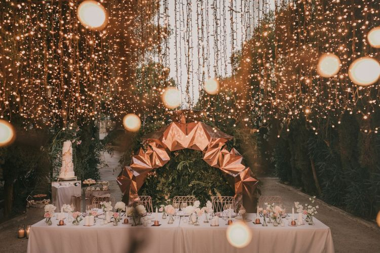 Top Table Wedding Decor with Fairy Light Canopy, Copper Geometric Structure, Flower Stems in Vases and Geode Wedding Cake
