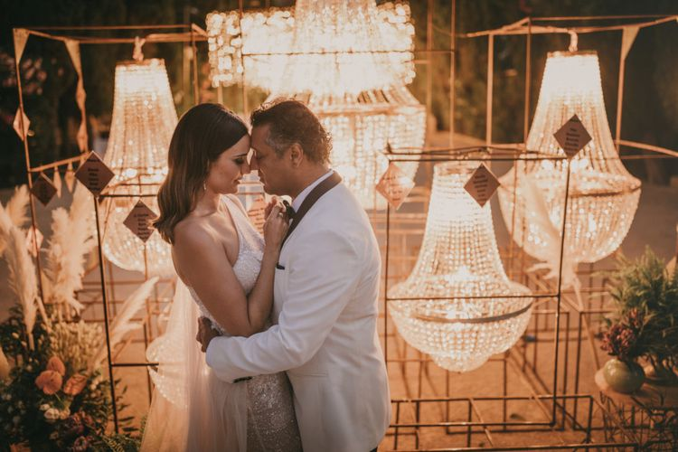 Bride in One Shoulder Wedding Dress and Groom in White Dinner Jacket Standing in Front of Their Chandelier Table Plan