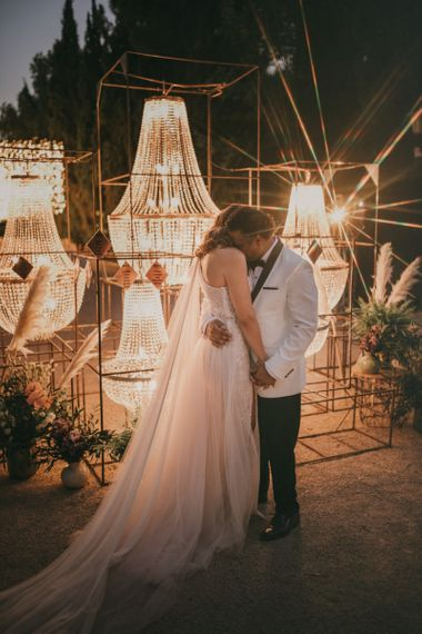 Groom in White Dinner Jacket Embracing his Bride in Front of a Chandelier Table Plan