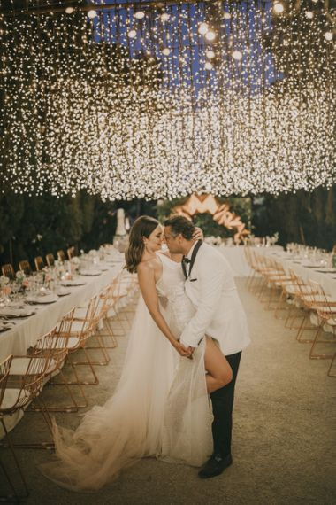 Bride in One Shoulder Muse by Berta Wedding Dress and Groom in White Dinner Jacket Posing Under a Fairy Light Canopy