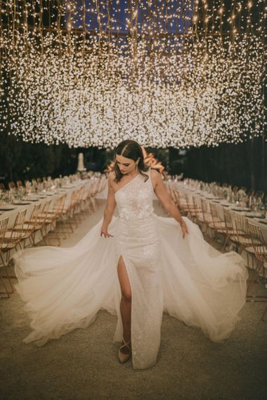 Bride in One Shoulder Muse by Berta Wedding Dress with Front Split Under a Fairy Light Canopy
