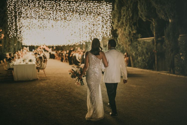 Bride in One Shoulder Muse by Berta Wedding Dress and Groom in White Dinner Jacket Entering the Outdoor Wedding Reception with Fairy Light Canopy