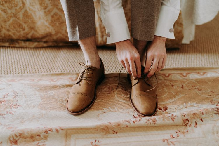 Groom putting on brown wedding shoes