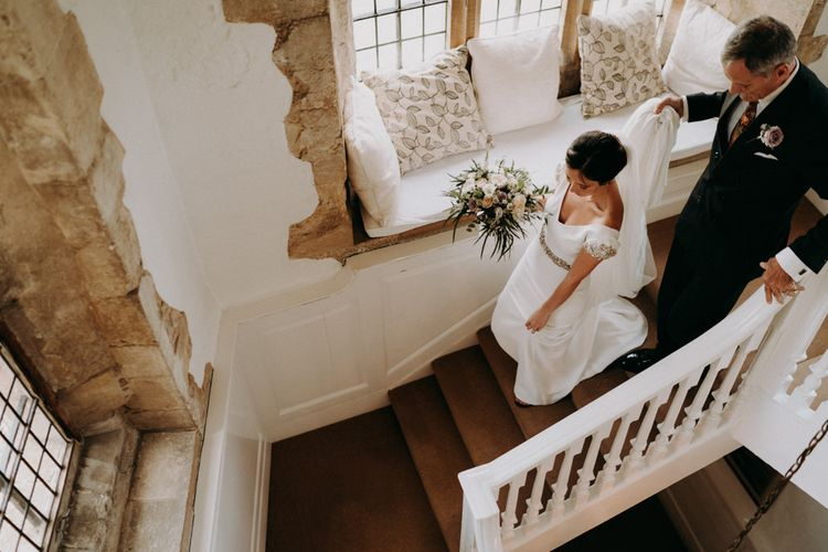 Bride walking down the stairs in minimalist wedding dress