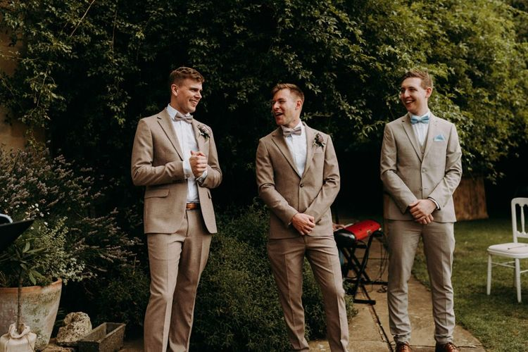 Groomsmen in beige suits with bow ties