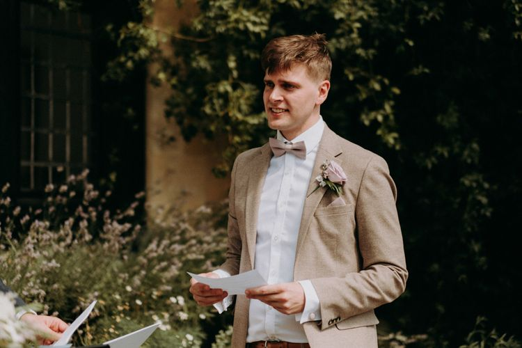 Groom in Beige wedding suit and bow tie reading his wedding vows