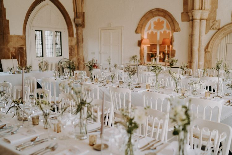 Wedding reception at Butley Priory with white chairs and green flowers