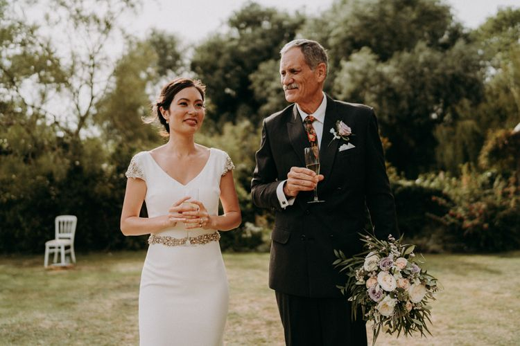 Bride in fitted Pronovias wedding dress standing with her father