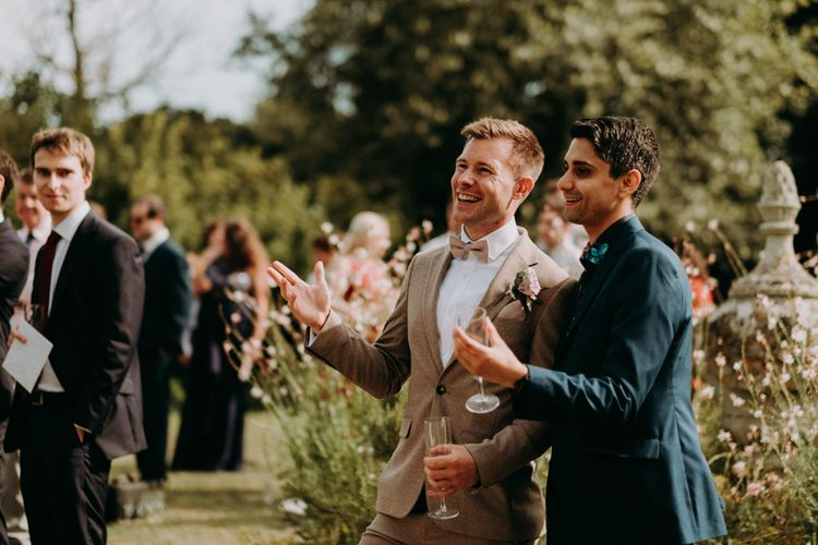 Groom and wedding guests laughing during the outdoor wedding speeches