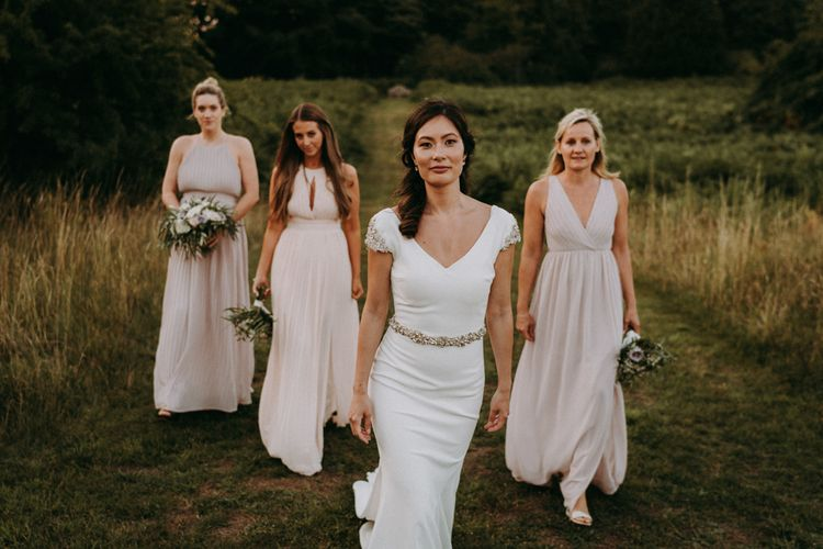Bridal party portrait with bride in Pronovias wedding dress and bridesmaids in pale pink dresses