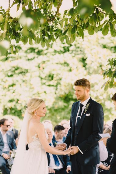 Wedding Ceremony | Bride in Lace Illusion Neck  & Tulle Skirt Watters Gown |  Groom in Navy Dress2Kill Suit | Sophisticated Outdoor Wedding at Chateau Riguad, France with Neutral Colour Palette | Modern Vintage Weddings Photography