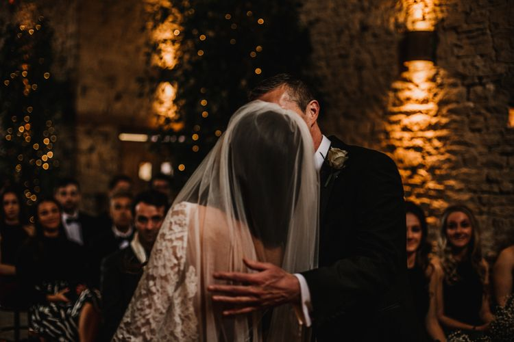 Groom Kissing his Bride at The Altar