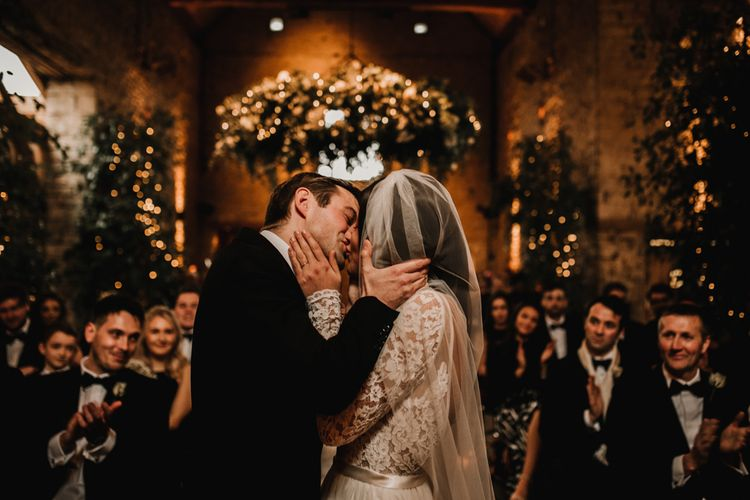 Bride and Groom Kissing at the Altar with Fairy Lights and Foliage Background