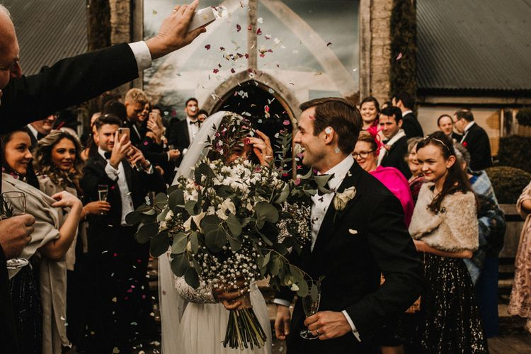 Confetti Moment with Bride in Made With Love Bridal Wedding Dress Holding a White and Green Bouquet and Groom in Tuxedo