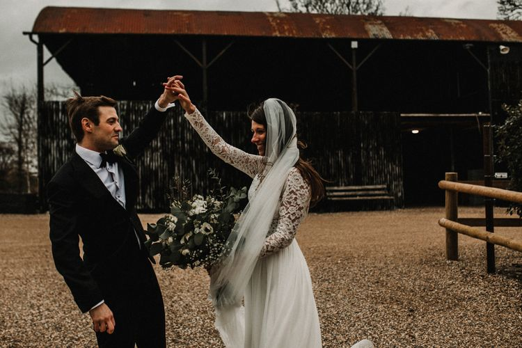 Groom in Tuxedo and Bow Tie Twirling his Bride in Made With Love Bridal Wedding Dress Holding a White and Green Bouquet