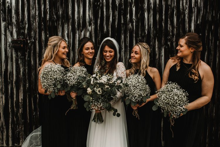 Bridal Party Portrait with Bridesmaids in Black Halter Neck Dresses Holding Gypsophila Bouquets and Bride in Made with Love Bridal Wedding Dress