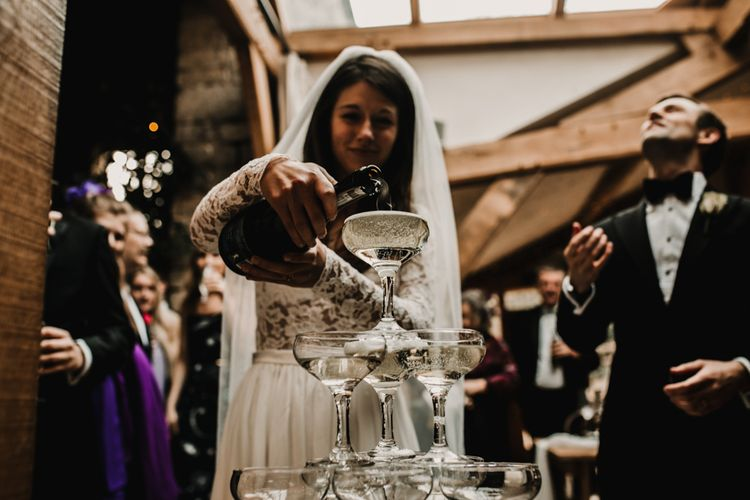 Bride Pouring Champagne Tower in Coupe Glasses