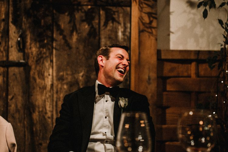 Groom in Tuxedo Laughing During Wedding Reception Speeches