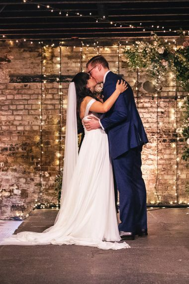 Bride in Martina Liana  Chiffon Bardot Wedding Dress and Groom in Navy Charles Tyrwhitt Suit Embracing at the Altar