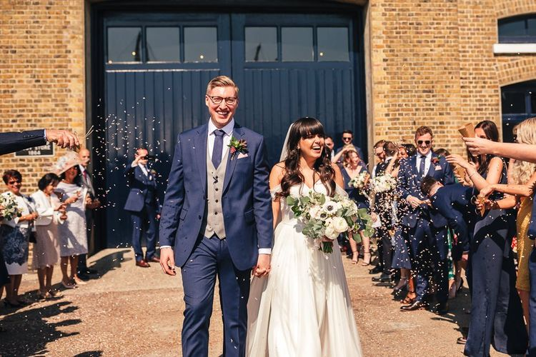 Confetti Moment with Bride in Martina Liana  Chiffon Bardot Wedding Dress and Groom in Navy Charles Tyrwhitt Suit and Grey Waistcoat