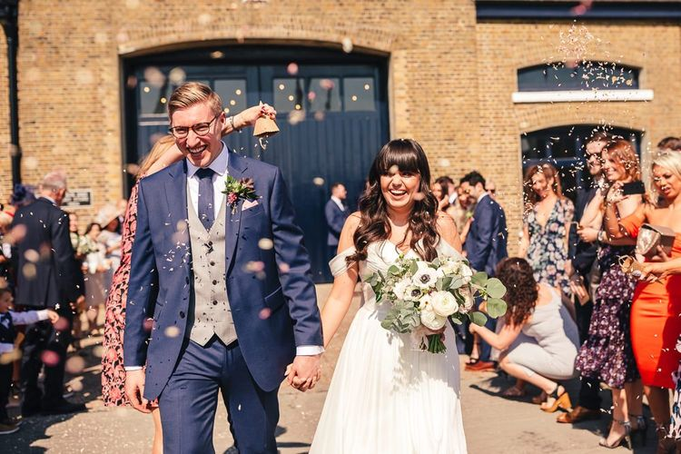 Confetti Exit with Bride in Martina Liana  Chiffon Bardot Wedding Dress and Groom in Navy Charles Tyrwhitt Suit and Grey Waistcoat