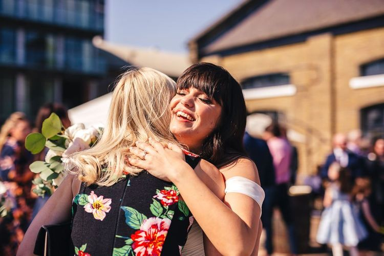 Beautiful Bride with Fringe Hugging a Wedding Guest