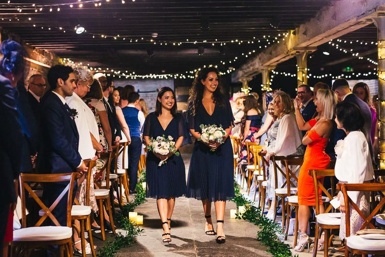 Bridesmaids in Navy Dresses Walking Down The Aisle Lined in Greenery and Candles
