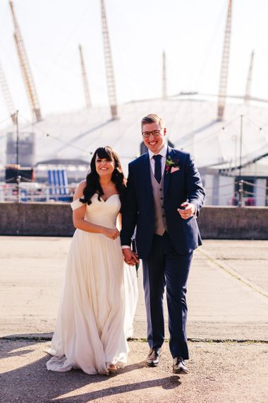 Bride in Martina Liana Chiffon Wedding Dress with Bardot Sleeves and Groom in Navy Charles Tyrwhitt Suit on London Dock