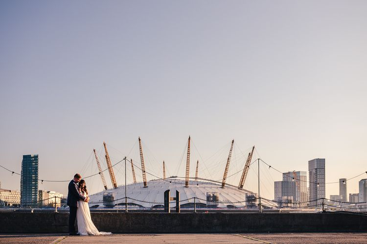 Bride in Martina Liana Chiffon Wedding Dress with Bardot Sleeves and Groom in Navy Charles Tyrwhitt Suit in Front of O2 Arena