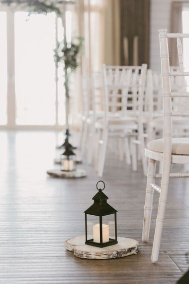 Barra Castle wedding ceremony decor with lanterns and rustic tree slices