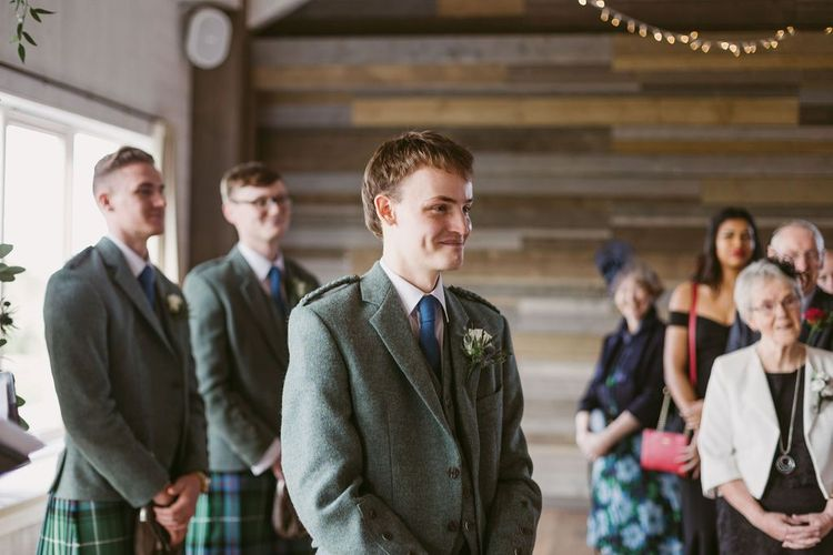 Groom in kilt waits for bride at aisle