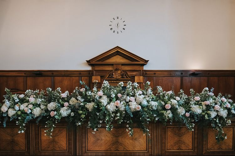 Blush and White Flowers with Foliage Altar Arrangement | Wedding Ceremony at Town Hall Hotel | Statement Floral Arrangement Altar and Potted Plants with Copper Frame Table Plan and Lace Jacket | Miss Gen Photography