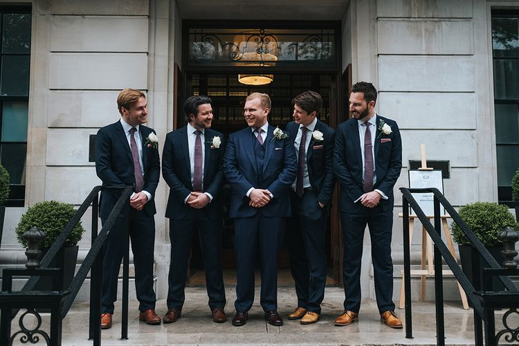 Groom in Navy Three-Piece Suit with Blush Pocket Square | Groomsmen in Navy Two-Pieve Suits | Town Hall Hotel Wedding | Statement Floral Arrangement Altar and Potted Plants with Copper Frame Table Plan and Lace Jacket | Miss Gen Photography