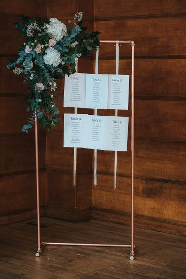Copper Frame Table Plan | Gold Ribbon | Floral Arrangement of White Hydrangeas, Blush Roses and Foliage | Statement Floral Arrangement Altar and Potted Plants with Copper Frame Table Plan and Lace Jacket | Miss Gen Photography
