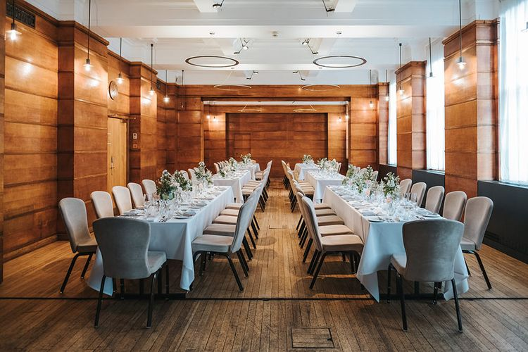 Long Banquet Tables | Grey Chairs | Blush Roses and Foliage in Bud Vases | Wooden-Clad Room at Town Hall Hotel | Statement Floral Arrangement Altar and Potted Plants with Copper Frame Table Plan and Lace Jacket | Miss Gen Photography