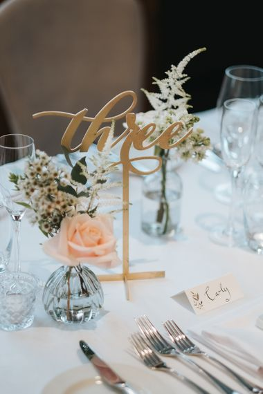 Gold Calligraphy Table Numbers | Blush Roses and Foliage in Bud Vases | Papier Place Cards | Statement Floral Arrangement Altar and Potted Plants with Copper Frame Table Plan and Lace Jacket | Miss Gen Photography