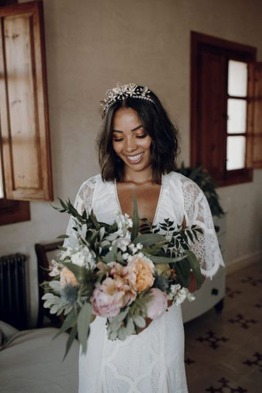 Boho bride in Grace Loves Lace wedding dress and Tilly Thomas Lux headband  holding her bouquet