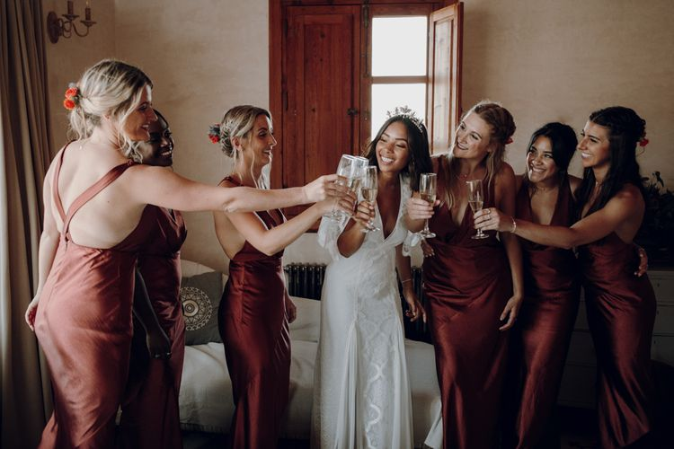 bride and bridal party sipping champagne on wedding morning with bride in Lace Loves Lace dress