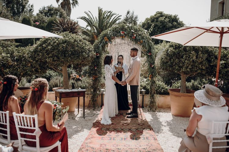 Bride and groom exchanging vows at destination wedding with bride in Grace Loves Lace dress