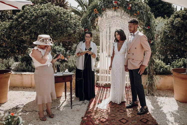 Outdoor wedding ceremony with floral arch, hanging macrame and Moroccan rugs