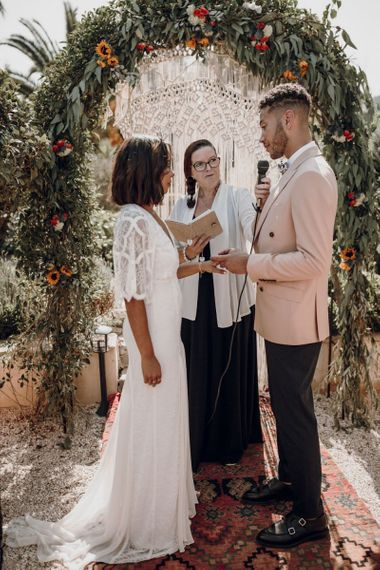 Bride and groom exchanging wedding rings during the ceremony with bride in Grace Loves Lace dress