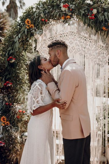 Groom on pale pink blazer kissing his bride in a Grace Loves Lace wedding dress