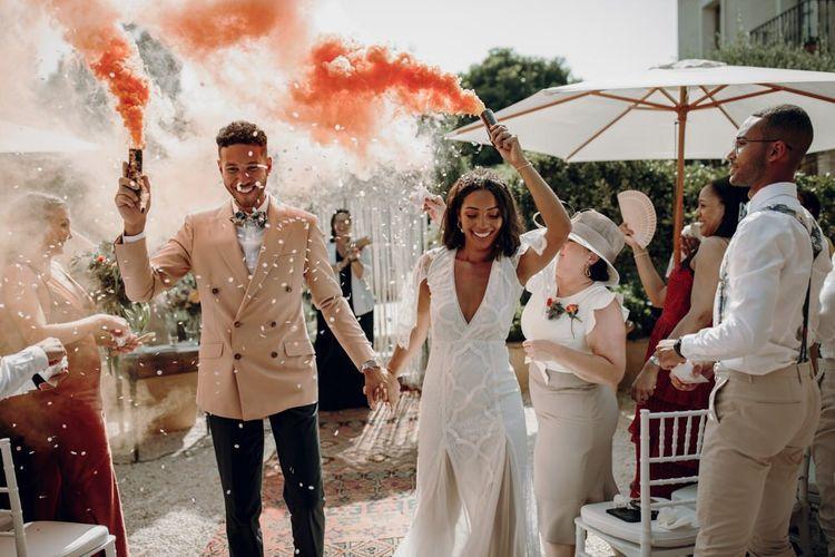 Boho bride and groom holding orange smoke bombs