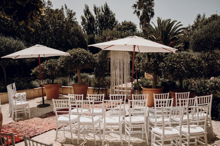 Outdoor wedding ceremony with parasols and macrame backdrop
