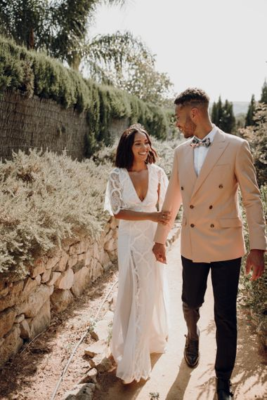 Stylish groom in double breasted blazer and bride in grace loves lace walking hand in hand