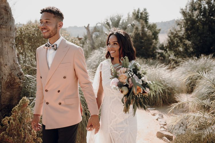 Groom in pink blazer and floral bow tie holding his brides hand in Spain