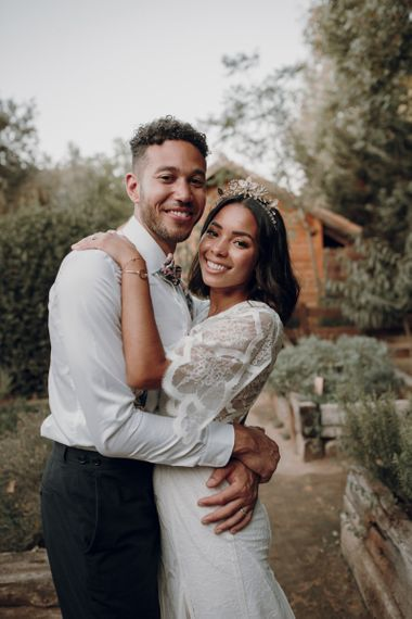 Boho bride and groom embracing with bride in Tilly Thomas Lux crown
