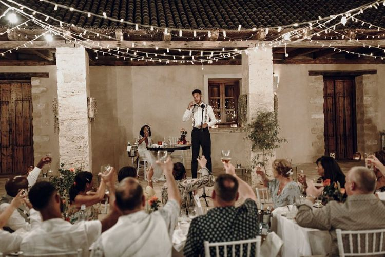 Groom in floral braces and bow tie giving his wedding speech