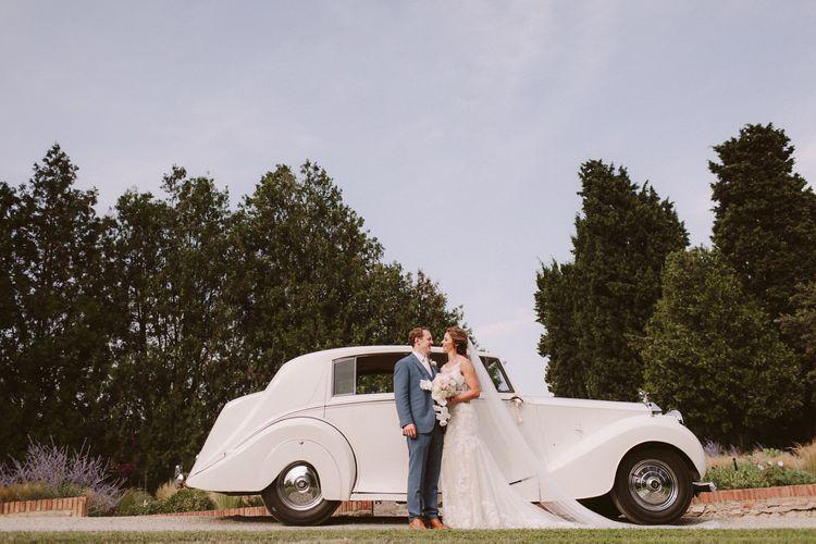Bride in Essense of Australia wedding dress  with groom by classic wedding car